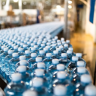 Zbliżenie butelek z wodą na przenośniku taśmowym w przemyśle, selektywne skupienie