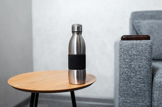 Zbliżenie: butelka termiczna ze stali nierdzewnej wielokrotnego użytku na drewnianym stole przy szarej ścianie w pobliżu sofy.