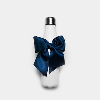Zbliżenie: butelka wody termo ze stali wielokrotnego użytku z niebieską kokardą jak prezent, na białym tle.