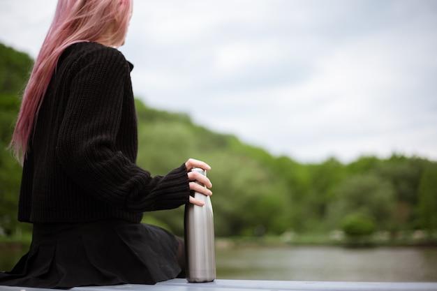 Zbliżenie: butelka ze stali nierdzewnej w ręku młoda dziewczyna z różowymi włosami.