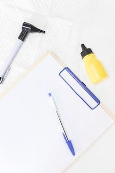 Zbliżenie butelki medycyny; otoskop i długopis ze schowkiem