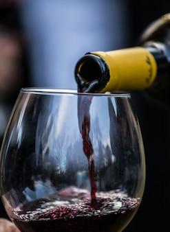 Zbliżenie butelki wina służącej w szklanym kieliszku