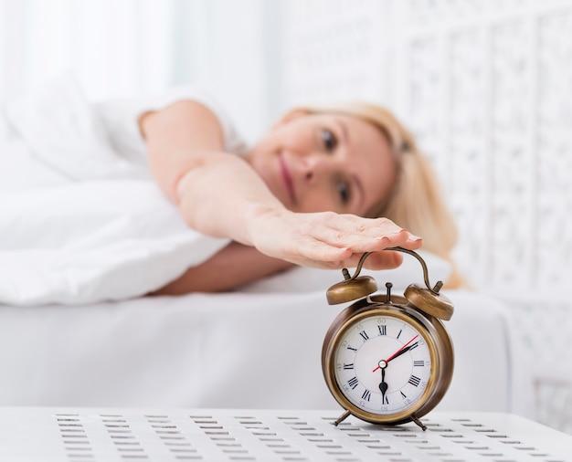 Zbliżenie całkiem dojrzała kobieta, osiągając, aby zatrzymać alarm