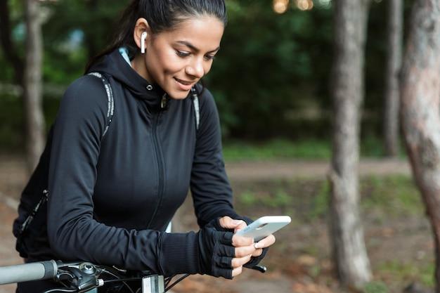 Zbliżenie całkiem młoda kobieta fitness, jazda na rowerze w parku, słuchanie muzyki przez słuchawki, trzymając telefon komórkowy