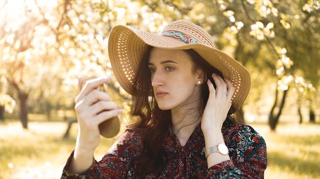 Zbliżenie całkiem młoda kobieta w kapeluszu ustalania jej makijażu, patrząc w lustro na zewnątrz