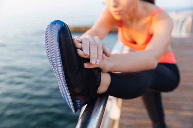 Zbliżenie całkiem młoda sportsmenka ćwicząca i rozciągająca nogi na zewnątrz