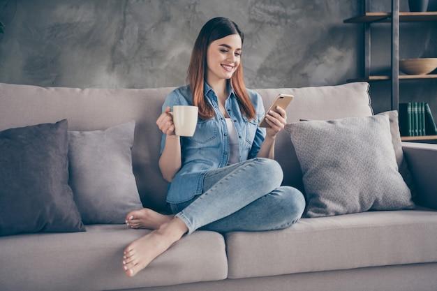 Zbliżenie całkiem urocza lisica pani siedzieć kanapa pić kawę czat telefon