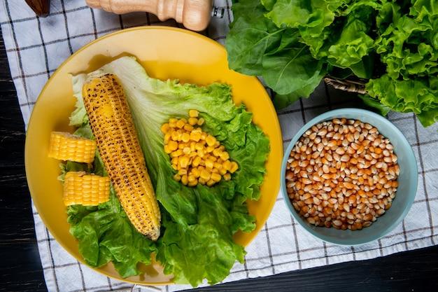 Zbliżenie całych i pokrojonych ziaren kukurydzy i kukurydzy z sałatą w talerzu i szpinakiem na kraciastej tkaninie