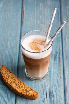 Zbliżenie cappuccino z mlekiem i ciastkiem