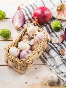 Zbliżenie cebuli; brukselki; ząbki czosnku i tkaniny w kratkę wzór na drewnianym stole
