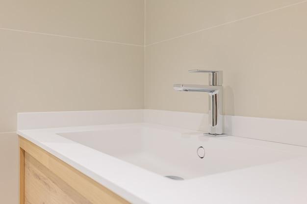 Zbliżenie: ceramiczna umywalka na drewnianej szafce pod umywalkę z nowoczesnym metalowym kranem w łazience.