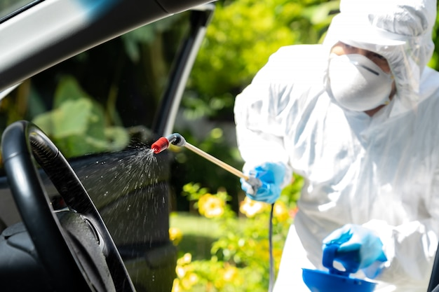 Zbliżenie chemicznego rozpylania alkoholu we wnętrzu samochodu w celu dezynfekcji i odkażenia koronawirusa covid-19 przez specjalistyczny środek czyszczący noszący środki ochrony indywidualnej śoi. nowa normalna koncepcja higieny.