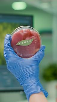 Zbliżenie chemika trzymającego w rękach próbkę wegańskiego mięsa wołowego