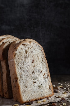 Zbliżenie chleb pełnoziarnisty w plasterkach na ciemne rustykalne drewniane tła bio składników