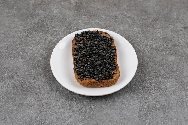 Zbliżenie chleba żytniego z czarnym kawiorem na białym chlebie