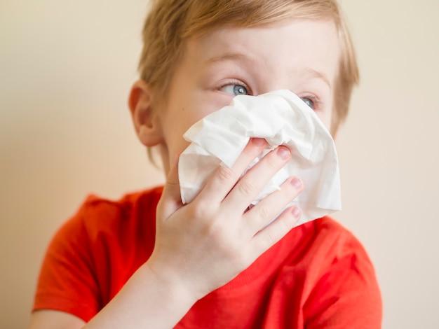 Zbliżenie chłopiec dmuchanie nosa