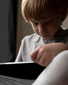 Zbliżenie: chłopiec siedzi w char i za pomocą tabletu