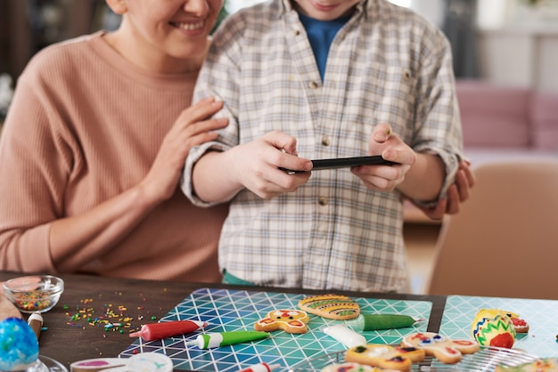 Zbliżenie: chłopiec używający telefonu komórkowego do robienia zdjęć domowych ciasteczek na stole z matką