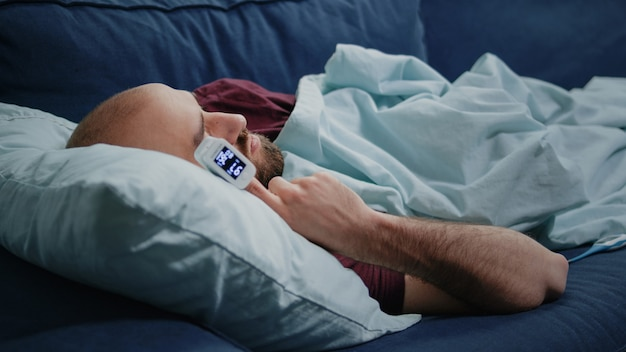 Zbliżenie chorego człowieka śpiącego na kanapie z oksymetrem na palcu