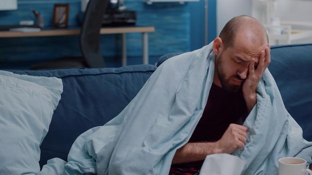 Zbliżenie chorego człowieka z bólem głowy, dmuchanie nosa za pomocą chusteczek