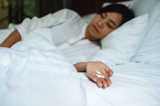 Zbliżenie chorej kobiety śpiące i leżącej na łóżku z białymi pigułkami w ręku