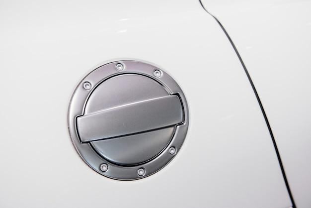 Zbliżenie chromowanej pokrywy zbiornika paliwa lub korka wlewu gazu białego samochodu sportowego z okrągłym metalowym szerokim wykończeniem i śrubami sześciokątnymi.