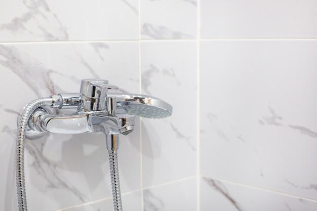 Zbliżenie chromowany kran w marmurowej łazience, widok z boku copyspace