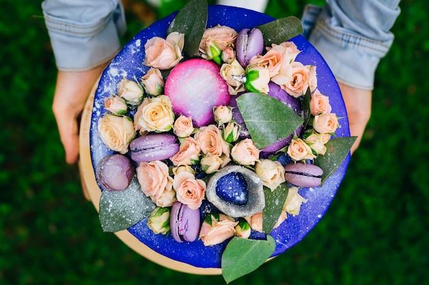 Zbliżenie ciasta ozdobionego żywymi różami z zielonymi liśćmi i makaronikami