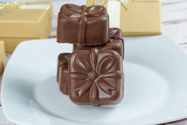 Zbliżenie ciastka z miodu brazylijskiego ułożone. otoczony złotymi pudełkami na prezenty.