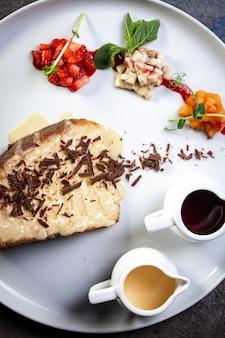 Zbliżenie ciasto miodowe z kawałkami czekolady i jagodami widok z góry