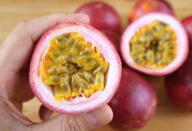 Zbliżenie cięcia świeżych dojrzałych owoców męczennicy w ręku z rozmyty stos całych owoców w tle
