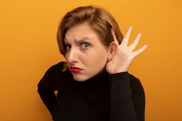 Zbliżenie ciekawa młoda blondynka trzymająca rękę w talii, kładąc kolejną rękę za uchem, robiąc, że nie słyszę, jak gest na białym tle na pomarańczowej ścianie