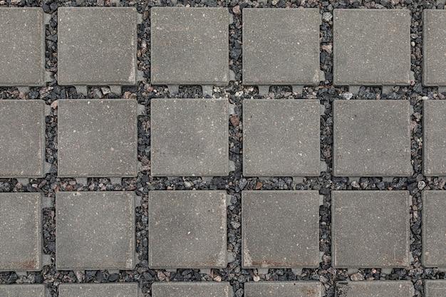 Zbliżenie: ciemnoszary kwadratowy płaski kamień ze żwirem w szczelinach
