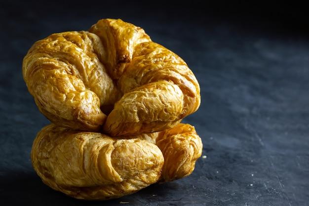 Zbliżenie croissant na stole w ciemnym tle. skopiuj miejsce na tekst.