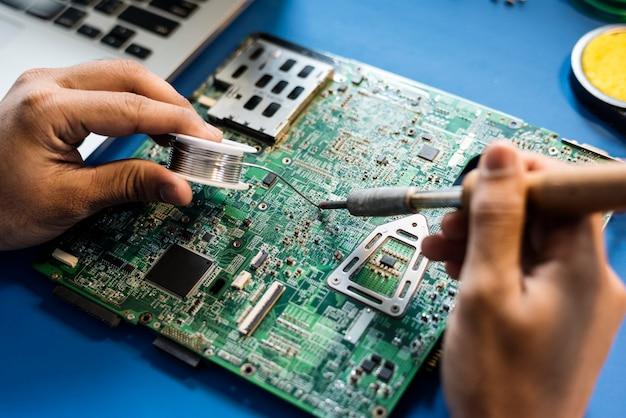 Zbliżenie cynowy lutowanie z elektronika obwodu deską