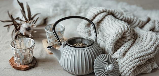 Zbliżenie czajnika w skandynawskim stylu z herbatą z dzianinowym elementem i detalami dekoracyjnymi