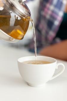 Zbliżenie czajnika z gorącą wodą do robienia herbaty z zielonymi ziołami