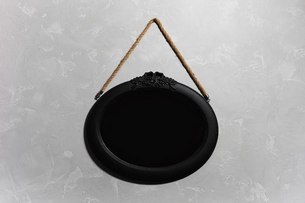 Zbliżenie: czarne drewniane lustro wiszące na szarej ścianie z teksturą.