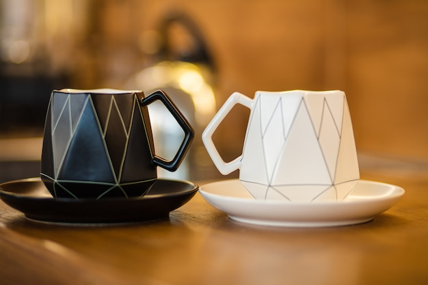 Zbliżenie czarnego ceramicznego kubka na czarnym talerzu i białego ceramicznego kubka na białym talerzu znajduje się na brązowym stole