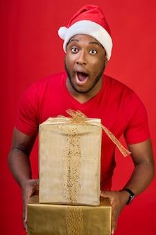Zbliżenie czarnego faceta z otwartymi ustami w kapeluszu świętego mikołaja dającego prezent na boże narodzenie