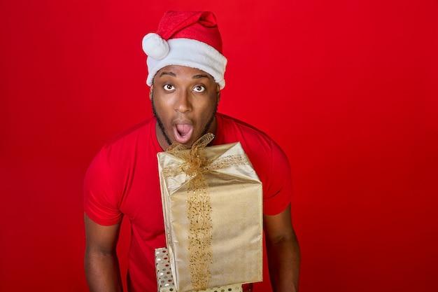 Zbliżenie czarnego faceta z otwartymi ustami w kapeluszu świętego mikołaja dającego świąteczny prezent w złotym opakowaniu
