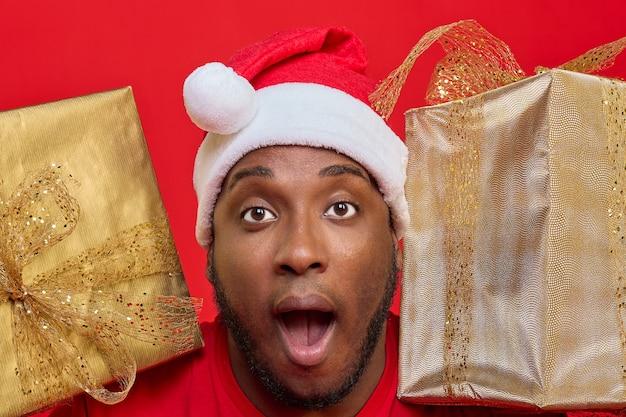 Zbliżenie czarnego faceta z otwartymi ustami w kapeluszu świętego mikołaja, trzymającego na ramionach prezenty świąteczne