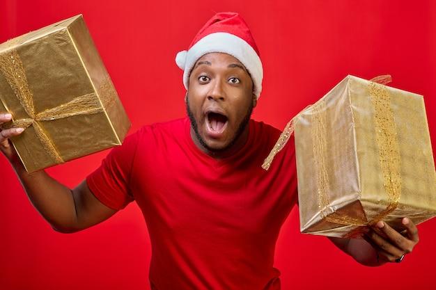 Zbliżenie czarnego faceta z otwartymi ustami w kapeluszu świętego mikołaja trzymającego prezenty świąteczne w złotym opakowaniu