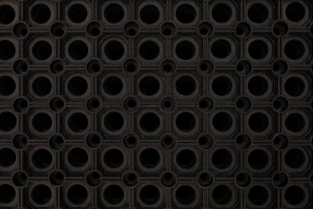 Zbliżenie czarnej gumowej maty podłogowej.
