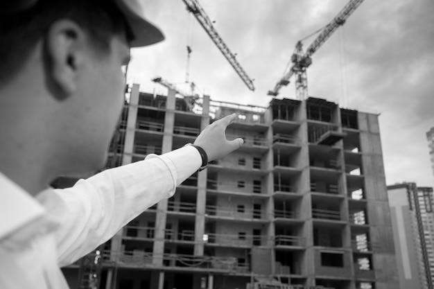 Zbliżenie czarno-biały obraz inżyniera budowlanego wskazując ręką na budynek w budowie