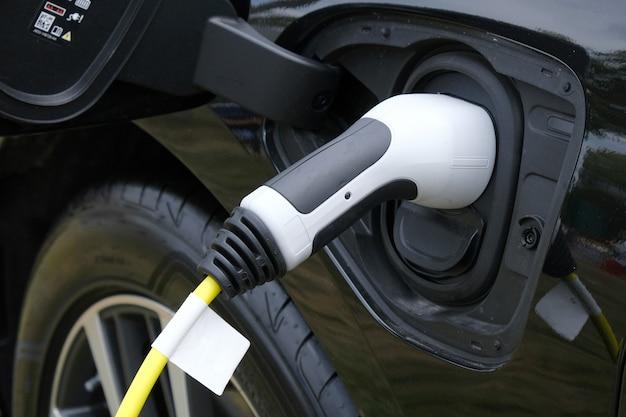 Zbliżenie czarny elektryczny samochód ładuje w staci.