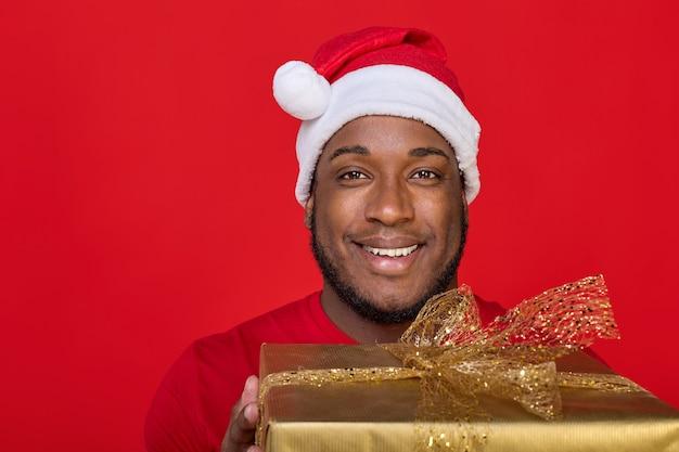 Zbliżenie czarny facet z uśmiechem toothy w kapeluszu santa dając prezent na boże narodzenie