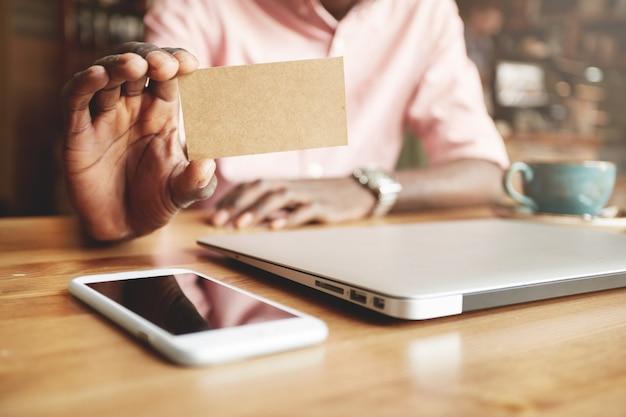 Zbliżenie czarny mężczyzna ręce trzymając puste pergamin wizytówkę