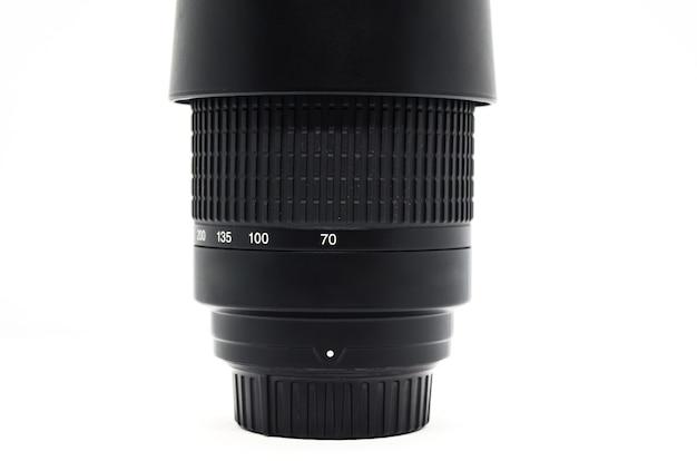 Zbliżenie: czarny pionowy obiektyw aparatu na białym tle. skala regulacji ogniskowej. sprzęt fotograficzny.