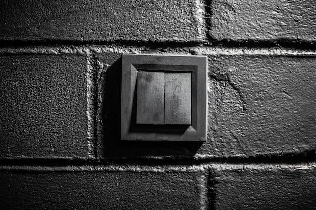 Zbliżenie: czarny przełącznik elektryczny na ścianie z teksturą cegły.